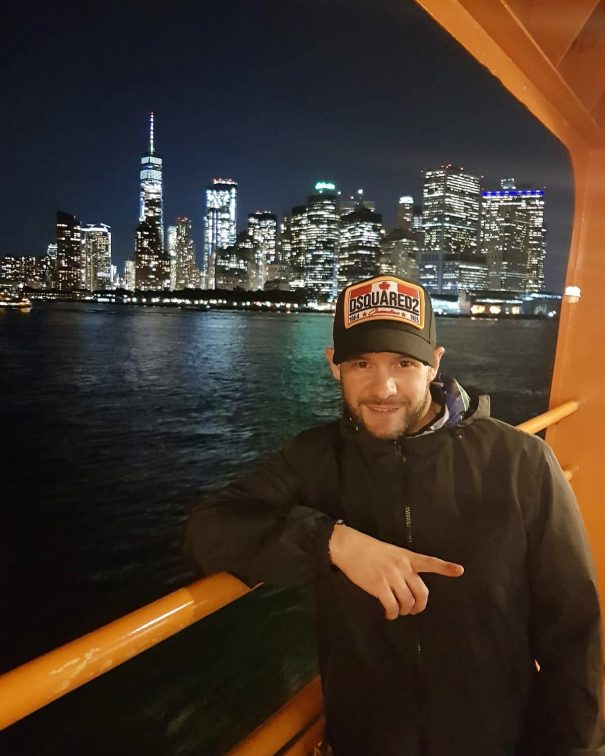 Harry Shotta standing on boat with New York behind him.